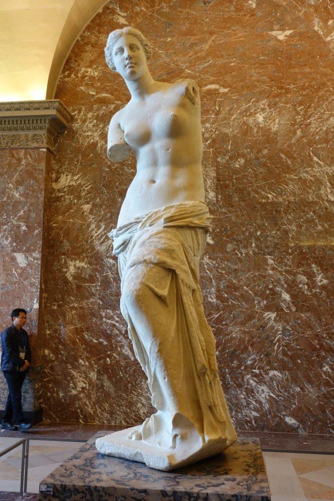 Afrodita, llamada Venus de Milo. Es la diosa del amor y la belleza. Algunos dicen que si tuviera los brazos, con la mano derecha se estaría sosteniendo la túnica y con la izquierda una manzana